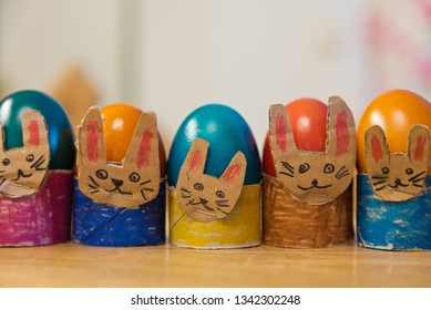 Series of children's homemade colorful easter egg cups in the shape of rabbit faces painted in vivid colors.