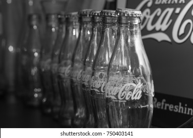 Series of Coca Cola bottles made of glass, with old fashioned design and a vintage tray on the background. Cairate, Italy - September 2009.