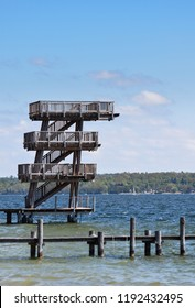 A series of diving boards stretching above the blue water of lake Ammersee in the town of Utting