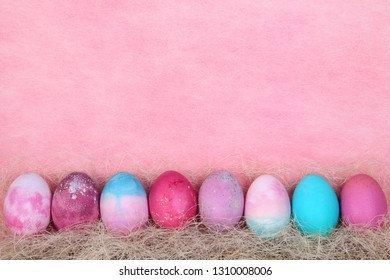 A series of easter watercolor eggs on a sisal. Bright colored eggs on a pale-pink background. Easter card.