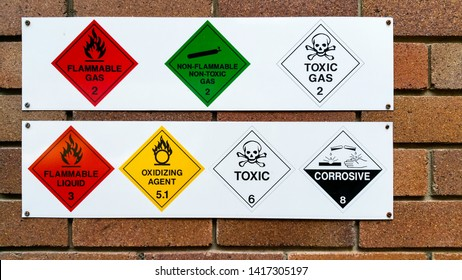 A series of flammable, non-flammable, toxic, corrosive and oxidizing gas and chemical safety symbols attached to a brick wall for public safety and cautionary purposes.
