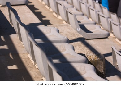 A series of gray plastic seats in an outdoor grandstand