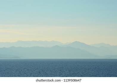 A series of hills appear blue in the late afternoon light. Before them stretches a blue ocean. The sky above is blue, with some white clouds.