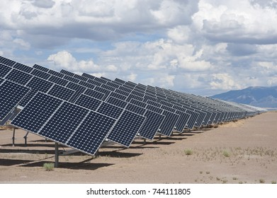 A series of large solar panels forms a symmetrical line at a power plant in the San Luis Valley of central Colorado.  These panels utilize a tracking system to follow the sun.
