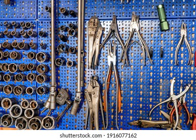 A SERIES OF MECHANICAL TOOLS INCLUDING VARIOUS PLIERS, SOCKET WRENCHES, SCISSORS AND EXTRACTORS.THE ALL HANGED FROM THE BLUE BACKGROUND. PERFECT SHOE FOR ARTS, TRADES AND WORKS.