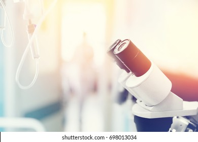 A series of microscopes and a dropper background in the hospital. Concept medicine, biology, research, education. With a glare of sunlight