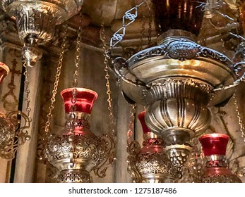 A series of oil lamps illuminate the interior of a portion of the Church of the Holy Sepulchre in the Old City of Jerusalem in Israel.
