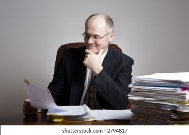 Series of an older businessman at desk.