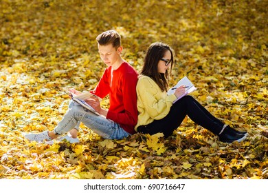 Series photo of beautiful young brunette woman in sunglasses and young man in red shirt sitting back to back on a fallen autumn leaves in a park and reading a book
