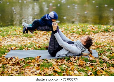 Series photo of sporty mother with infant baby boy workout together in autumn park. Infant boy with mother sitting on yoga mat in autumn park. Multitasking, healthy life and recreation concept