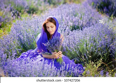 Series. Portrait of beautiful romantic woman in fairy field of lavender with bouquet