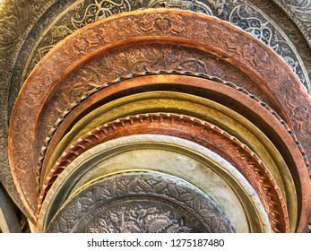 A series of round metal platters with detailed designs are for sale in a shop in the bazaar of the Old City of Jerusalem in Israel.