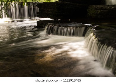 A series of small waterfalls in a forest.  Old Stone Fort State Archaeological Park, Manchester, TN, USA.