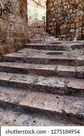 A series of steps climbs up a hill between buildings in the Arab Quarter of the Old City of Jerusalem in Israel.