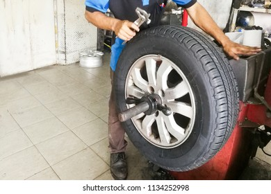 Series of technician performing car wheel tire balancing in garage