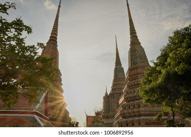 Series of temple in Wat Pho in Bangkok with sun rays and cloud formation.