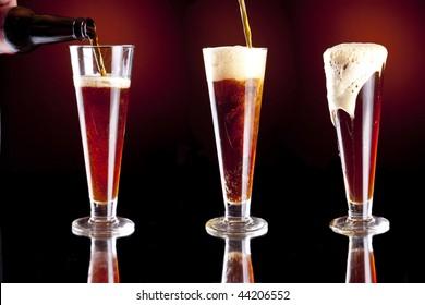 Series of three pilsner glasses being filled full of dark red beer.