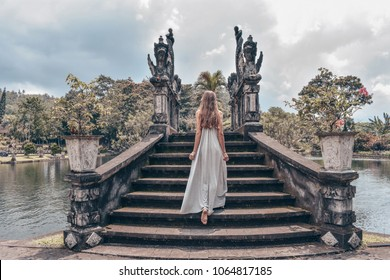 series traveling girl in Asia. beautiful girl with long dark hair in elegant grey dress posing on old bridge in Tirta Gangga water temple in Bali