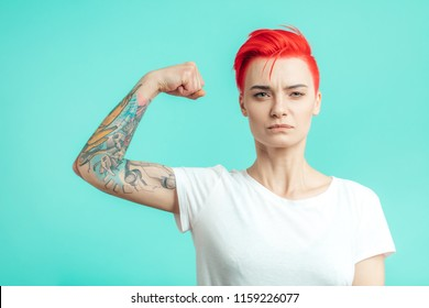 serioous fit glamour girl with pink hair shows biceps. sport , fitness, welness, health care concept. copy space