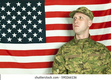 Serios  young soldier stand against  American flag, looking direct. Portrait
