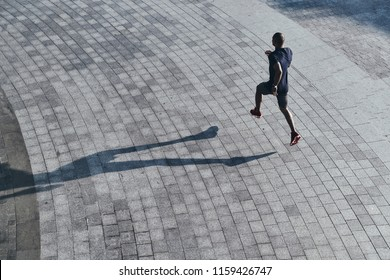 Serious about staying in shape. Top view of young African man in sports clothing jogging while exercising outdoors