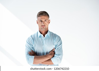 serious adult man in shirt looking at camera with crossed arms isolated on white