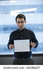 Serious adult office employee showing clear sheet of paper, Vertical indoors shot