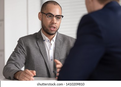 Serious african american bank investment advisor insurance broker lawyer in suit consulting client customer at business advice meeting talking to male customer explaining business loan deal benefits