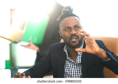 Serious African American businessman with collected rasta hair at work in office