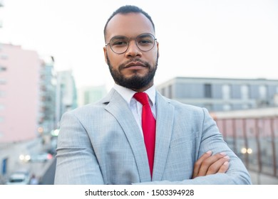 Serious African American businessman. Portrait of confident young businessman in formal wear standing with crossed arms and looking at camera. Professional occupation concept