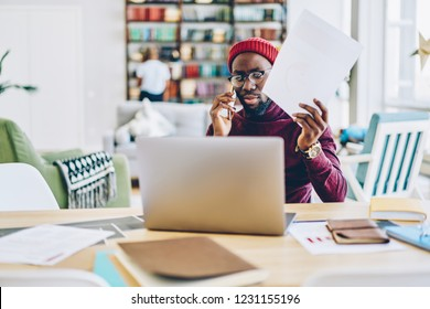 Serious african american male freelancer concentrated on remote job at home holding papers and making phone call at desktop, pensive dark skinned man concentrated on reading online news on netbook