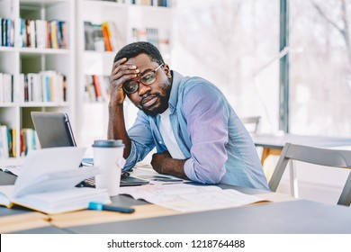 Serious african american male student sitting at desktop while watching tutorial on laptop computer tired during exam preparation, unhappy dark skinned freelancer disappointed with doring content