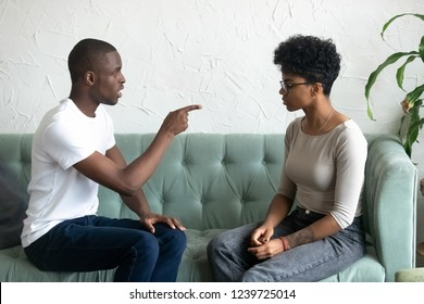 Serious African American man blaming upset woman, pointing finger at her, strict brother talking with sister, sitting together on couch, couple talking about relationships, break up concept