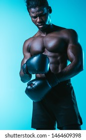 serious african american sportsman fixing boxing glove on blue background