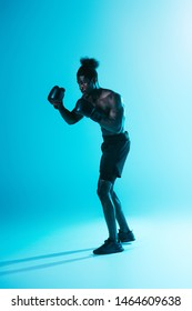 serious african american sportsman in shorts and sneakers boxing on blue background