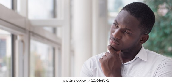 serious african business man thinking or planning; portrait of thoughtful black man thinking, planning, considering, finding a good idea; young adult african man model, banner crop format