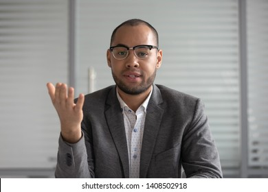 Serious african businessman entrepreneur in suit talking to camera, mixed race coach webinar speaker teacher trainer shooting vlog online business training look at webcam make conference video call