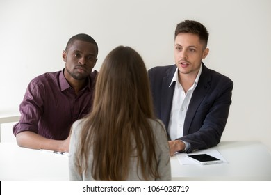 Serious african and caucasian hr managers interviewing female job applicant, diverse recruiters listening to candidate answering question at hiring negotiations, recruiting, first impression concept