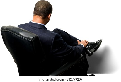 Serious African man with short black hair in business formal outfit with hands holding leg - Isolated