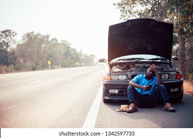 Serious african man using smartphone and holding his head by hands standing near his old broken car  with raised hood on the highway road