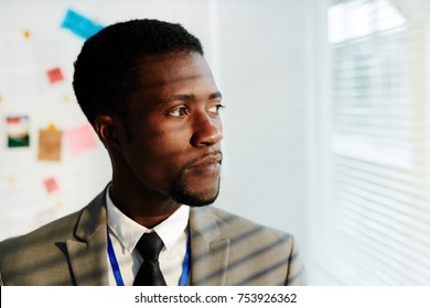 Serious African-american businessman looking through window in office