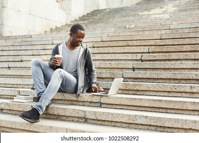 Serious african-american man with laptop and take away coffee sitting on stairs. Casual student preparing for exams with computer in university campus. Education and technology concept.