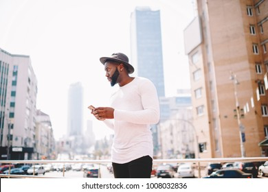 Serious afro american man in trendy outfit sending messages while standing on urban setting background, thoughtful dark skinned hipster guy in hat using application for navigating in megalopolis