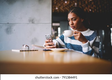 Serious afro american young woman doing shopping in web stores on modern smartphone via high speed internet connection resting in coffee shop interior with cup of tasty coffee in hand.Publicity area