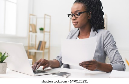 Serious Afro Business Lady Using Laptop Working With Papers In Modern Office. Copy Space