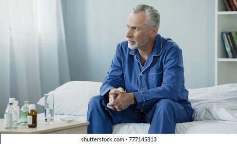Serious aged man sitting upset and pensive on bed at home, lonely sick person