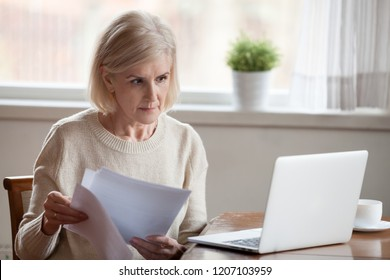 Serious aged woman holding documents, checking information at laptop online, concerned senior female managing bank insurance or loan papers, busy working at computer. Elderly and technology concept