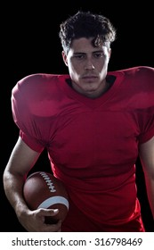 Serious American football player holding ball against black background
