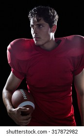 Serious American football player looking away holding ball against black background