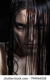 serious angry woman with wet black hair looking at camera